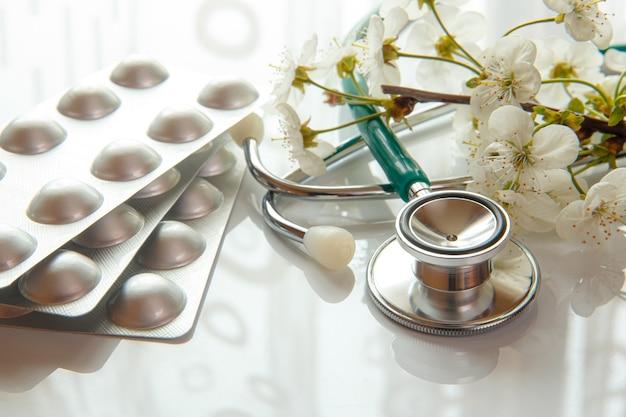 Stethoscoop en pillen met reflectie en witte bloemen