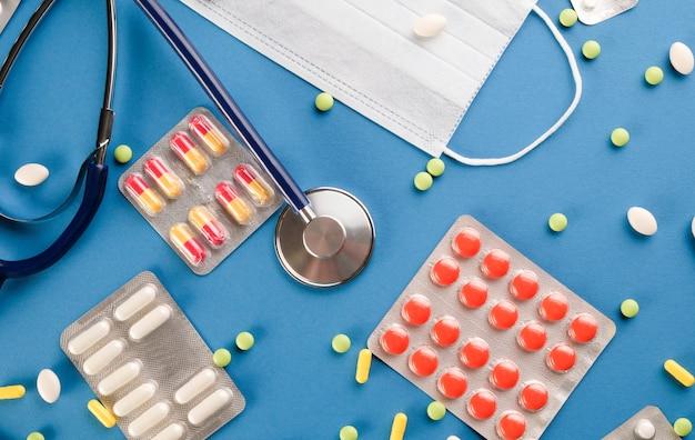 Stethoscoop en pillen op een blauwe tafel