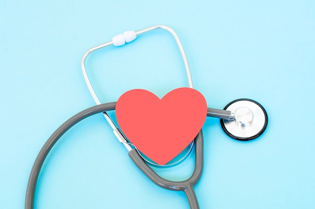 Stethoscoop en rode hartvorm op blauwe achtergrond, hart en gezondheidszorgconcept