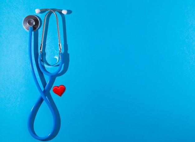 Stethoscoop en rood hart op blauwe achtergrond