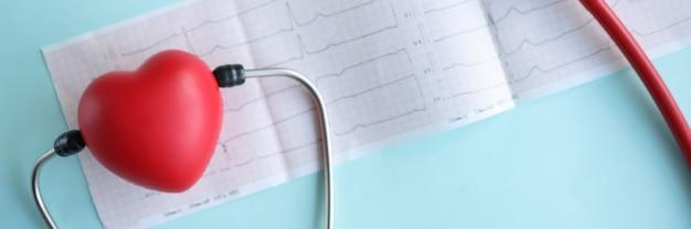 Stethoscoop en rood stuk speelgoed hart die op elektrocardiogram op blauwe close-up als achtergrond liggen