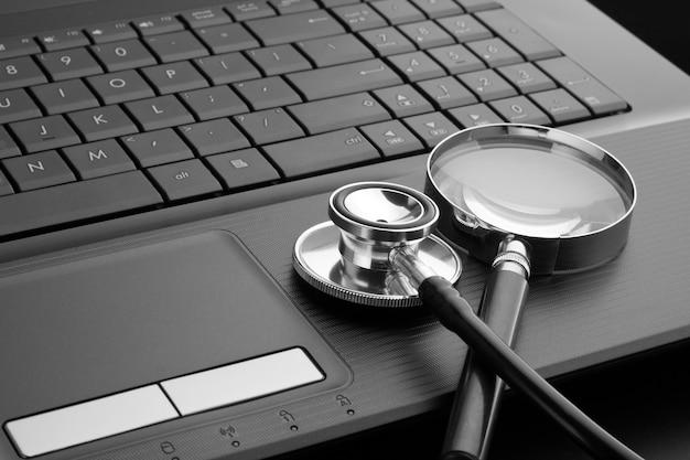 Stethoscoop en vergrootglas op laptop