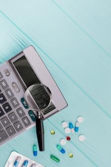 Stethoscoop en vergrootglas over een rekenmachinesymbool voor gezondheidszorgkosten of medische verzekering. kosten van de gezondheidszorg.