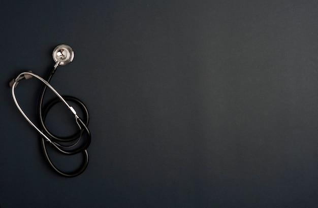 Stethoscoop geneeskunde accessoires, zwarte achtergrond met kopie ruimte.