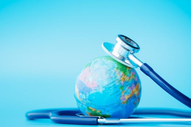 Stethoscoop gewikkeld rond de wereld op een blauwe achtergrond.