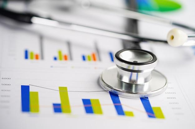 Stethoscoop, grafieken en grafieken spreadsheet papier, financiën, account, statistieken, investeringen, analytische onderzoeksdata economie spreadsheet en bedrijf bedrijfsconcept.