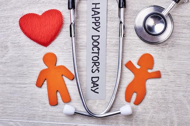 Stethoscoop, hart, stickmen op de achtergrond. gefeliciteerd met de dag van de dokter.