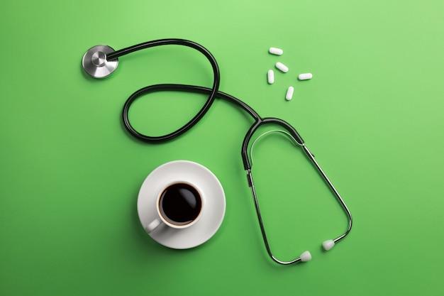 Stethoscoop in artsenbureau met kopkoffie en pillen. bovenaanzicht.