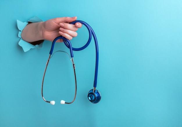Stethoscoop in een vrouwelijke hand op een blauwe achtergrond met een gat, medische concept