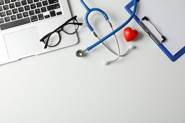 Stethoscoop, laptop, tablet, pen en hart op een witte achtergrond, ruimte voor tekst