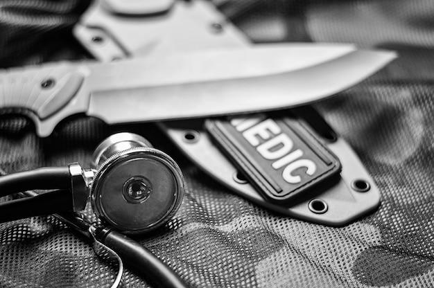 Stethoscoop ligt op het uniform van een amerikaanse soldaat. het concept van gezondheidszorg, militaire verzekering, staatszorg. bovenaanzicht. gemengde media