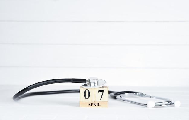 Stethoscoop met 7 april tekst houten blokkalender op witte houten achtergrond.