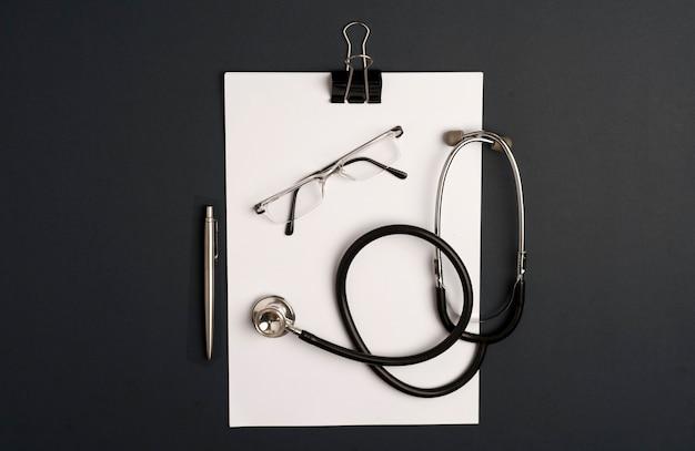 Stethoscoop met blocnote, bril en zilveren pen, zwarte achtergrond
