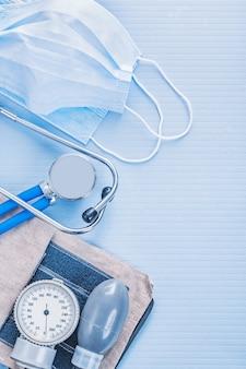Stethoscoop met bloeddrukmeter en maskers op blauwe muur medische concept