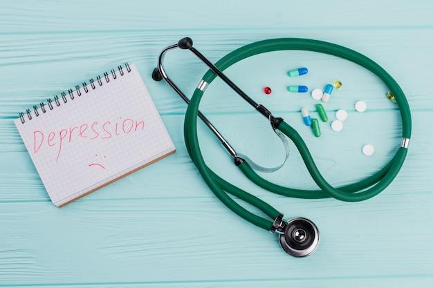 Stethoscoop met capsules op blauwe achtergrond. depressie geschreven op kladblok.