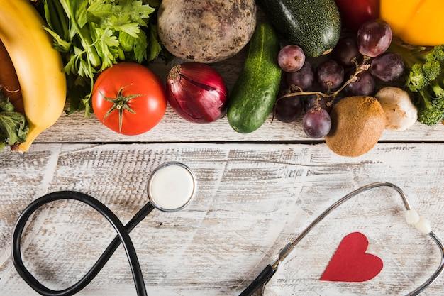 Stethoscoop met hartvorm dichtbij verse groenten op houten achtergrond