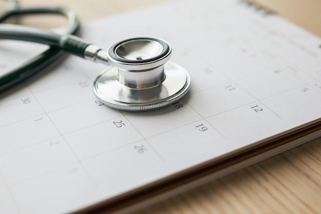 Stethoscoop met kalenderpagina datum op houten tafel