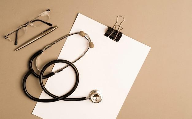 Stethoscoop met kladblok, glazen en pen, grijze achtergrond met kopie ruimte.