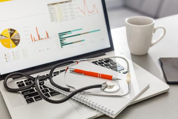 Stethoscoop met klembord en laptop op het bureau