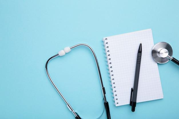 Stethoscoop met notitieboekje op blauw
