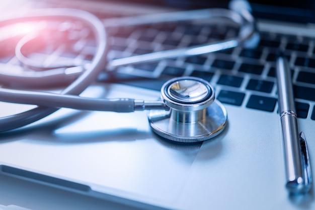 Stethoscoop met pen op laptop, stethoscoop voor arts check-up op medische gezondheidslaboratorium.