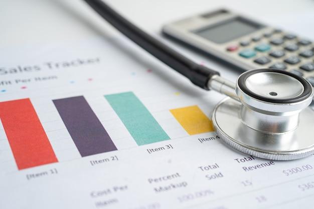 Stethoscoop met rekenmachine op grafiekpapier, financiën, account, statistiek, analytische economie bedrijfsconcept.