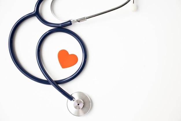Stethoscoop met rood hart geïsoleerd op achtergrond, bovenaanzicht. gezondheidszorg en geneeskunde concept