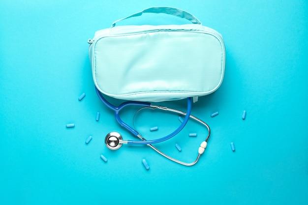 Stethoscoop met zak en pillen op kleur