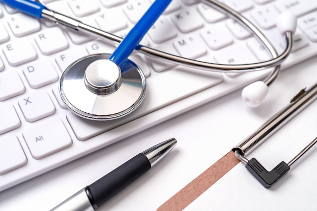 Stethoscoop op computertoetsenbord. arts schrijven medische zaak langdurige zorg behandeling concept close-up macro kopie ruimte