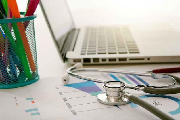 Stethoscoop op het bureau van de arts met medisch document en laptop
