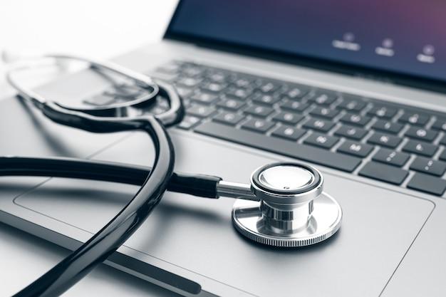 Stethoscoop op moderne laptopcomputer. online gezondheidszorg of telegeneeskunde concept
