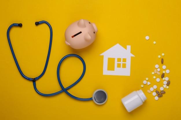 Stethoscoop, papieren huis, spaarvarken en pillen op geel, zorgverzekeringsconcept