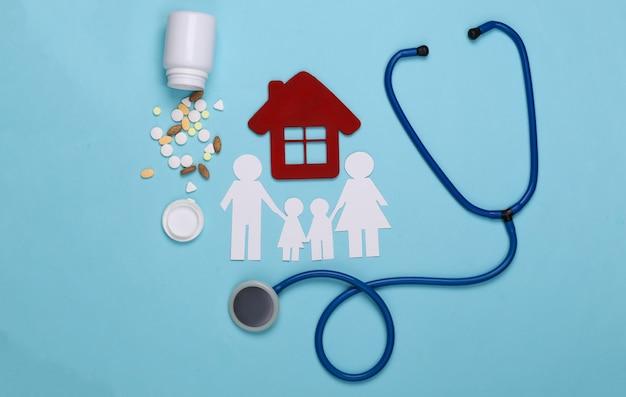 Stethoscoop, papieren kettingfamilie, huis, pillen op blauw, zorgverzekeringsconcept