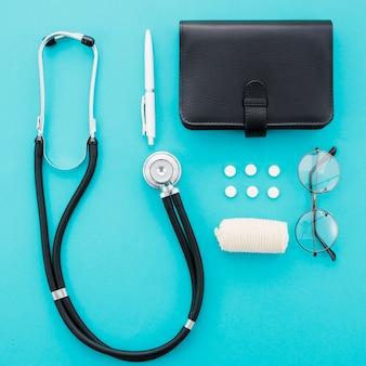 Stethoscoop; pen; pillen; dagboek; brillen en verband op blauwe achtergrond