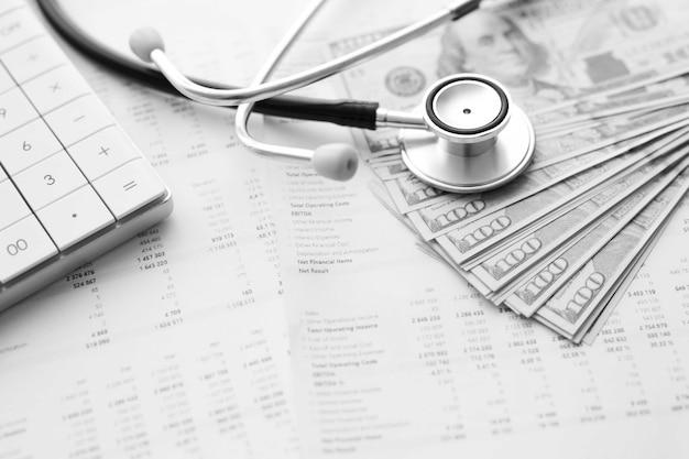 Stethoscoop, rekenmachine en geld contant op medische gegevens. concept van de kosten van de gezondheidszorg of medische verzekering