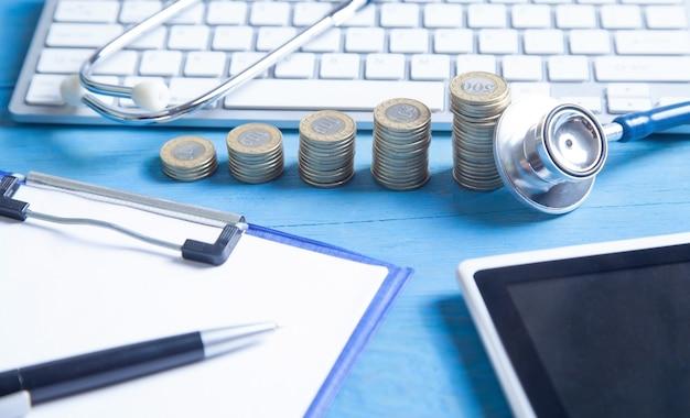 Stethoscoop, tablet, computertoetsenbord en munten op de blauwe achtergrond.