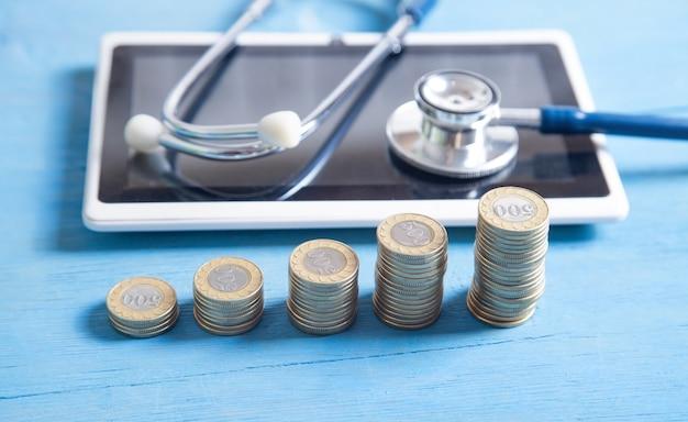 Stethoscoop, tablet en munten op de blauwe achtergrond.
