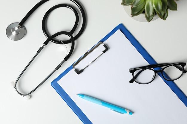 Stethoscoop, tablet, glazen, pen en plant op witte achtergrond, bovenaanzicht