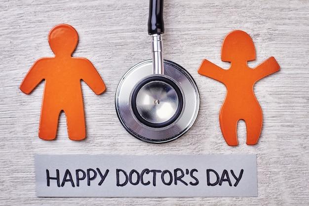 Stetoscoop, stickmen op houten oppervlak. fijne doktersdag.
