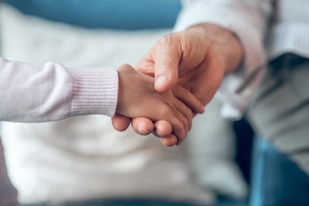 Steun. close-up foto van een mans hand die de hand van kinderen vasthoudt