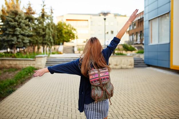 Stevig meisje met een rugzak die op de straat loopt