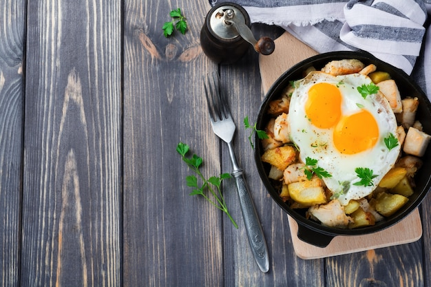 Stevig ontbijt. hash bruine aardappelen, kip, ui, peterselie, oregano en een gebakken ei in een koekenpan op de oude houten tafel. bovenaanzicht