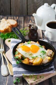 Stevig ontbijt. hash bruine aardappelen, kip, ui, peterselie, oregano en een gebakken ei in een koekenpan op de oude houten tafel.