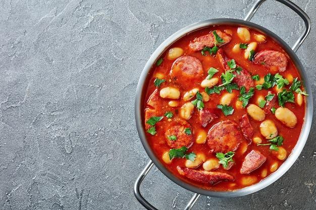 Stevige bonenstoofpot met worst, kruiden en specerijen in tomatensaus in een metalen braadpan