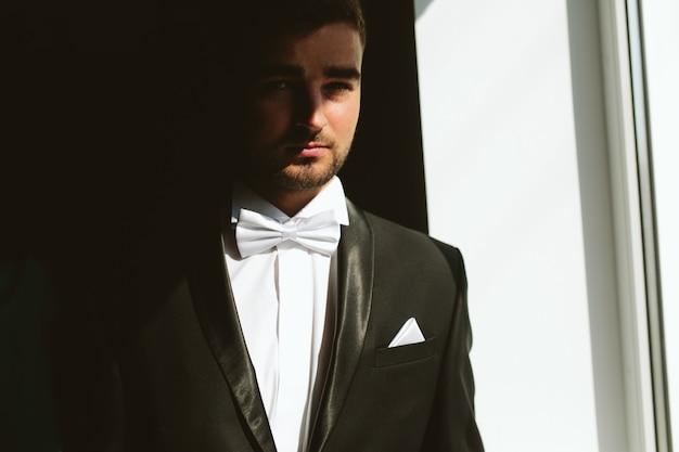 Stevige brunette bruidegom in zwart pak binnen zonlicht