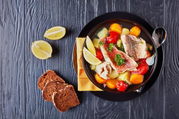 Stevige vissoep - griekse psarosoupa geserveerd in een zwarte kom op een houten tafel met servet en lepel, uitzicht van bovenaf, plat leggen