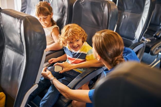Stewardess die een veiligheidsgordel vastmaakt van een gelukkige jongen