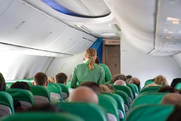 Stewardess, die passagiers bedient, biedt thee, koffie, eten aan tijdens de vlucht. interieur van het vliegtuig met de passagiers en de stewardess die met de trolley loopt.