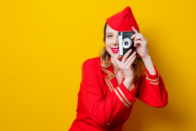 Stewardess dragen in rode uniform met fotocamera