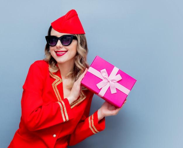 Stewardess dragen in rode uniform met vakantie cadeau bord
